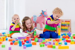 Happy preschool age children play with colorful plastic toy blocks. Creative kindergarten kids build a block tower. Montessori Toys for Infants and Toddlers. Siblings having fun playing together.